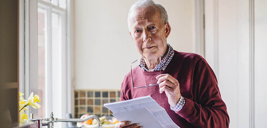 Senior man is standing in the kitchen of his home with bills in his hand, looking at the camera with a worried expression.