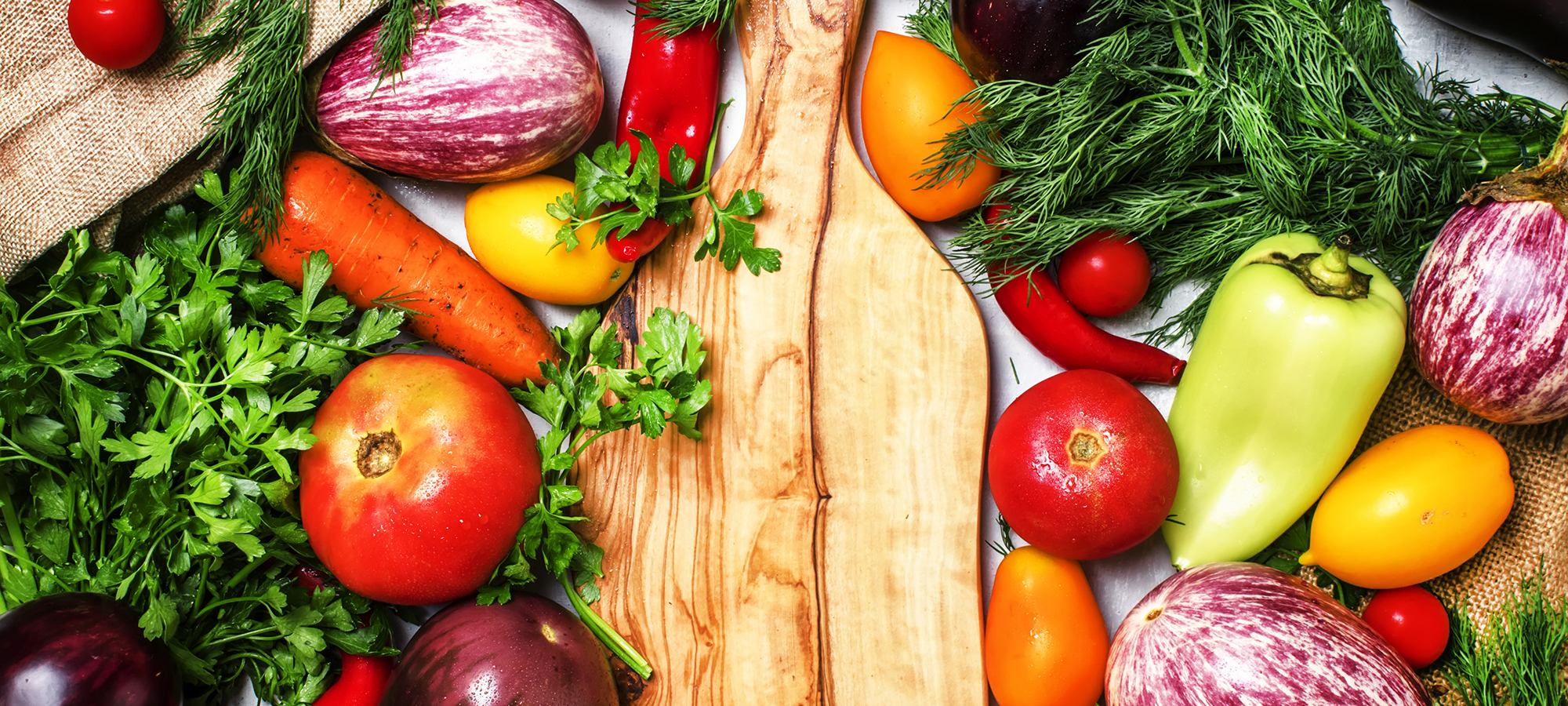 Cooking background, fresh vegetables and spicy herbs on a cutting board, top view