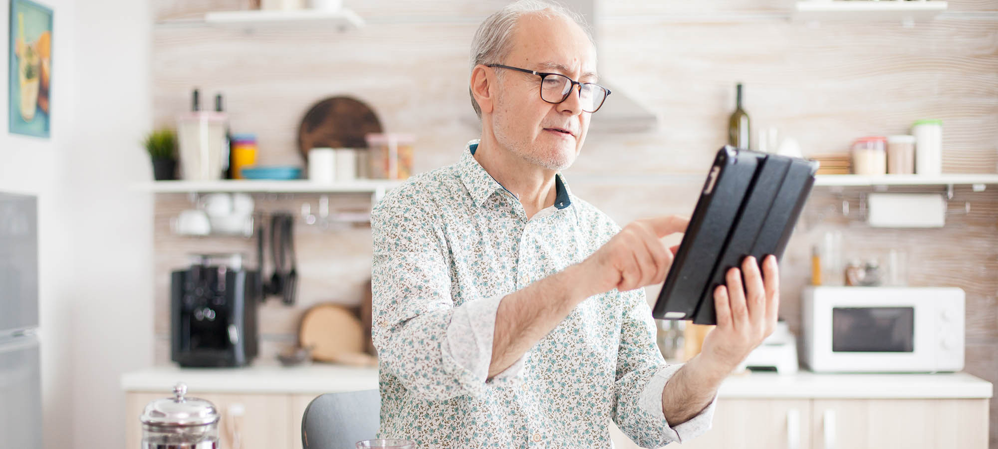 Happy elderly person with portable tablet PC in kitchen during breakfast. Senior person with tablet portable pad PC in retirement age using mobile apps, modern internet online information technology with touchscreen